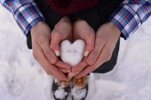 A couple holding hands in the shape of a heart with an engagement ring