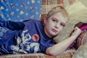 Unhappy child lying on a sofa